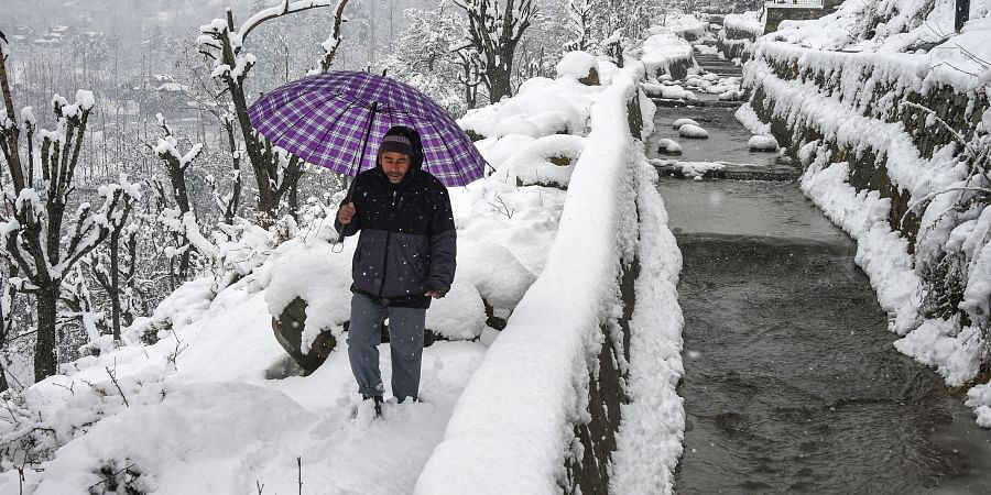 A man walks on a snow-covered path to climb up hill during snowfall on the outskirts of Srinagar Friday Dec. 13 2019. (Photo | PTI)