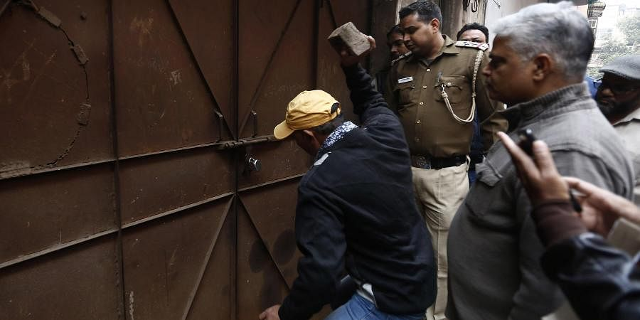 A MCD official breaks a lock before carrying out inspection at a factory at Anaj Mandi area on Wednesday. Express Photo by Arun Kumar P
