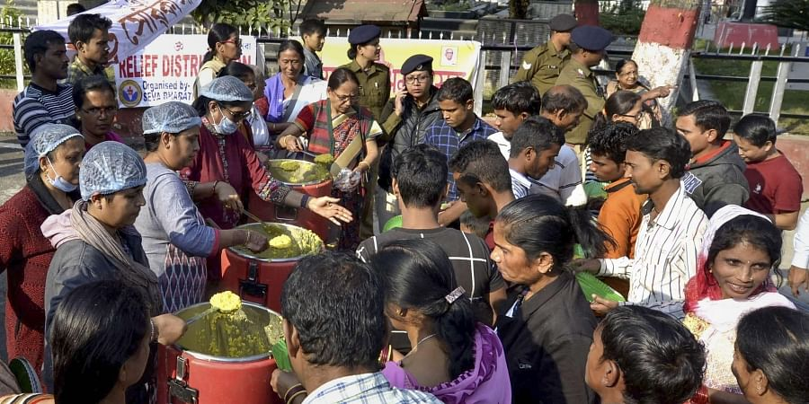 Volunteers of an NGO distribute free meal to stranded railway passengers as many trains were cancelled due to anti-Citizenship Amendment Bill protest in Guwahati Saturday Dec. 14 2019. (Photo | PTI)