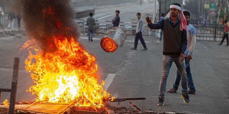 A protester throws a tin onto a fire made to block traffic in Gauhati.