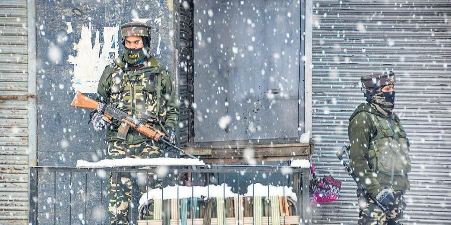 Paramilitary personnel stand guard amid biting cold and heavy snowfall in Srinagar on Friday.