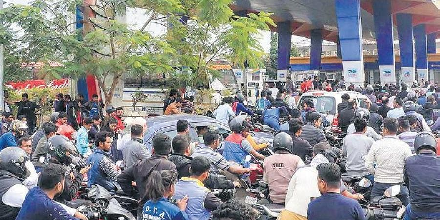 People queue up at a petrol pump during relaxed hours of curfew in Jorhat district of Assam on Friday.