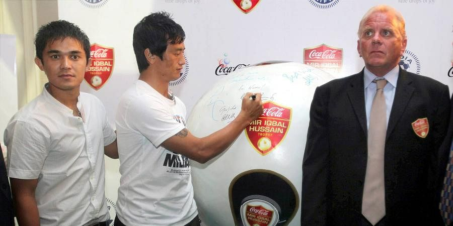 Then Indian skipper Bhaichung Bhutia signs the Mir Iqbal Hussain Trophy shaped like a giant football during announcement of Coca Cola's partnership with the All India Football Federation for the trophy in New Delhi on Tuesday. India coach Bob Houghton (R) and player Sunil Chhetri are also seen in the picture.