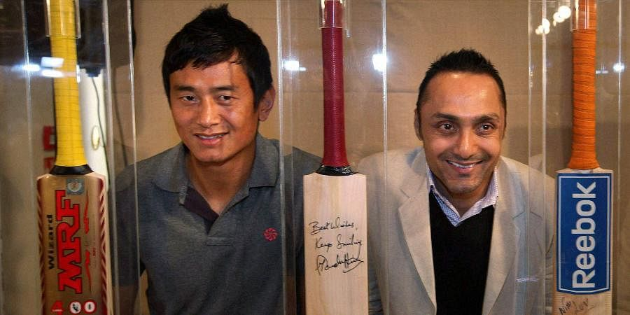 Former Indian football team captain Bhaichung Bhutia and actor Rahul Bose pose with the bats of Sachin Tendulkar, Brain Lara and MS Dhoni which will be auctioned, during a press conference in Mumbai.
