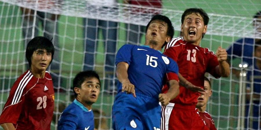 Indian football star Bhaichung Bhutia and Askarov Davron vie for the ball during the Nehru Cup match in New Delhi.
