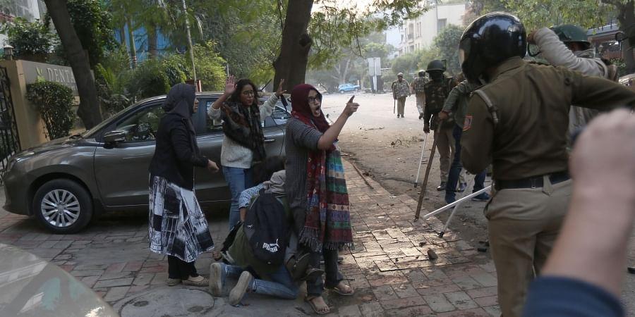 Girl students confront policemen during the lathicharge near Jamia Millia Islamia on Sunday. (EPS   Arun Kumar)