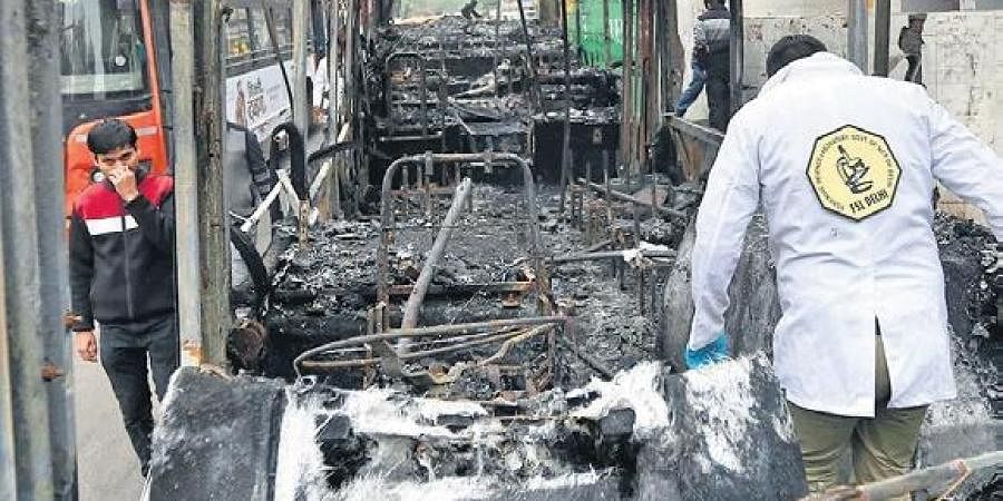 FSL officials inspect the charred remains of a bus that was torched by agitators at New Friends Colony, on Monday.