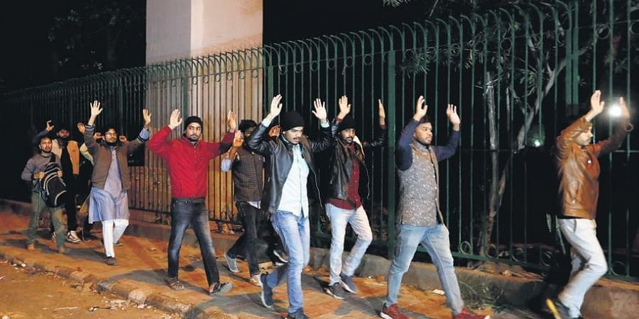Students being escorted out of Jamia Millia Islamia campus by police on Sunday.