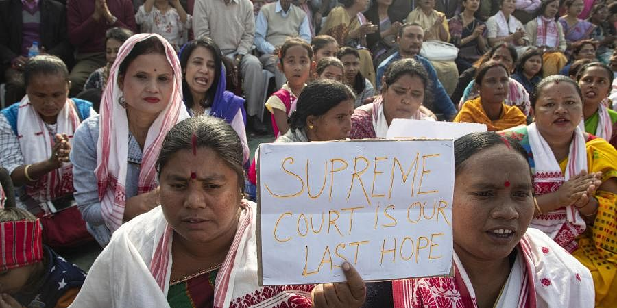 A woman holds a placard during a protest against the Citizenship Act in Gauhati on Thursday.