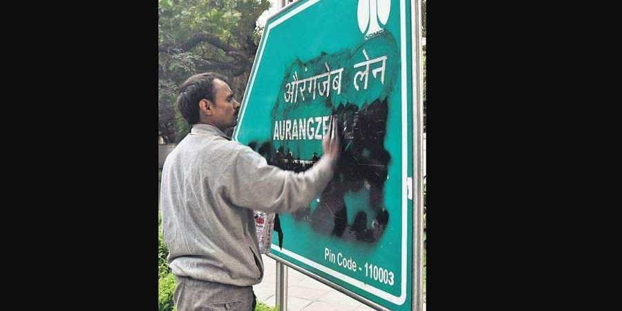 An NDMC worker cleans a board bearing the name of Aurangzeb Lane.