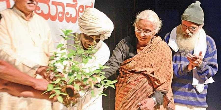 Theatre personality Prasanna (extreme right) and Narmada Bachao Andolan activist Medha Patkar water a plant during a Joint Convention Satyagraha For Sacred Economy in Bengaluru