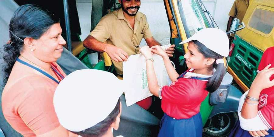 Students of Little Flower UP School in Kaloor, along with their teacher, selling  cloth bags made by them to autorickshaw drivers.