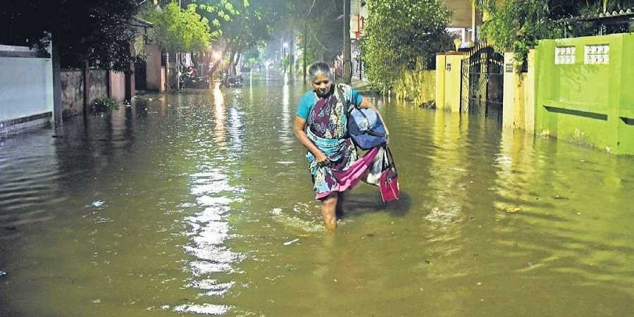 A woman struggles to walk through knee-deep water in the Chennai suburb of Korattur on Sunday evening.