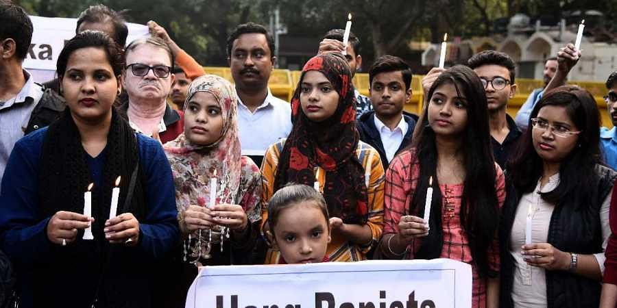 Youngsters during a candle light march held in solidarity of veterinary doctor at Jantar Mantar in New Delhi on Sunday.