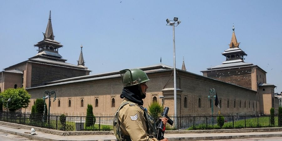 A security person stands guard outside closed Jamia Masjid in Srinagar