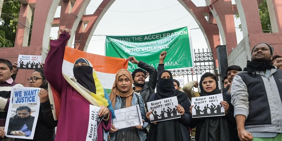 Protestors including students and local residents hold placards during a demonstration against the Citizenship Amendment Act outside Jamia Millia Islamia University