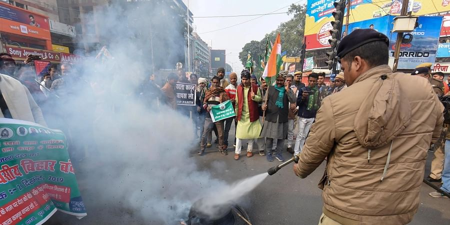 A Police personnel attempts to douse a burning tyre during a demonstration against NRC and Citizenship Amendment Act CAA in Patna Saturday Dec. 21 2019. (Photo | PTI)