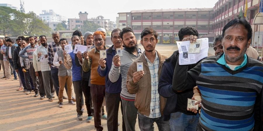 Voters stand in a queue displaying their voting card as they wait to cast their votes during the third phase of Jharkhand Assembly elections, in Ranchi