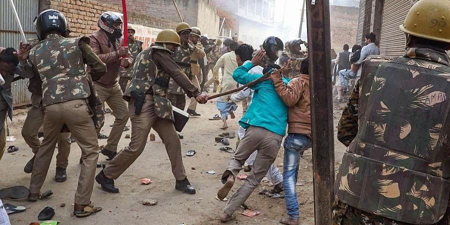 Police personnel baton charge on a commuter who rode too close to a barricade set up on a street in view of protests against Citizenship Amendment Act CAA in Jabalpur