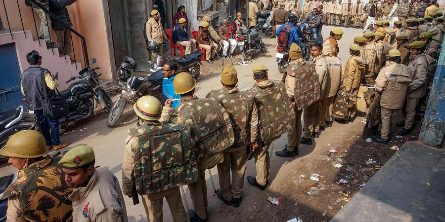 Police personnel guard a street during protests against Citizenship Amendment Act CAA in Varanasi Saturday Dec. 21 2019. (Photo | PTI)