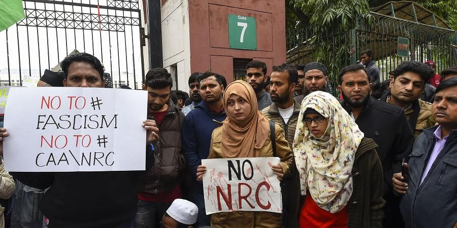 Students along with general public hold placards during a protest against the Citizenship Amendment Act CAA outside Jamia Millia Islamia University in New Delhi Tuesday Dec. 17 2019.