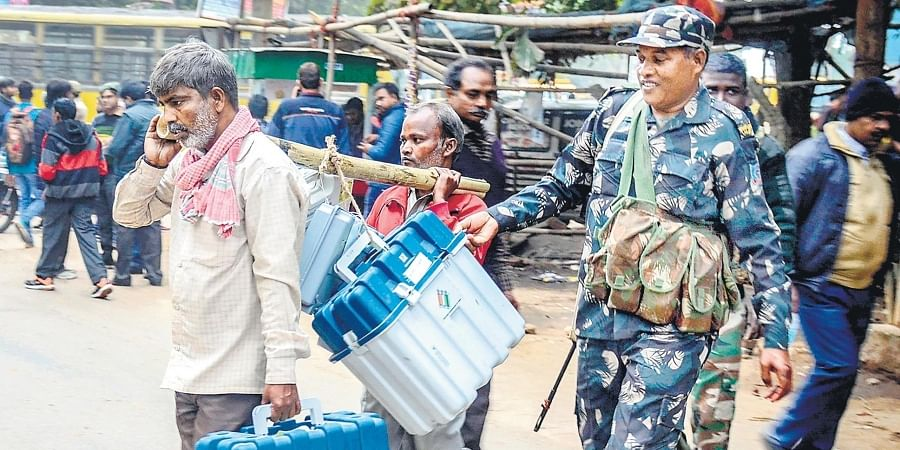 In Dhanbad, a poll staff carries EVM machines and other polling materials for of Jharkhand elections.