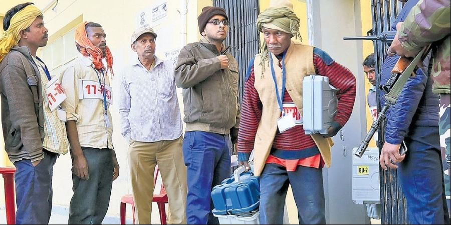 Election staff with EVMs and polling material on the eve of the final phase of Jharkhand elections in Godda on Thursday.