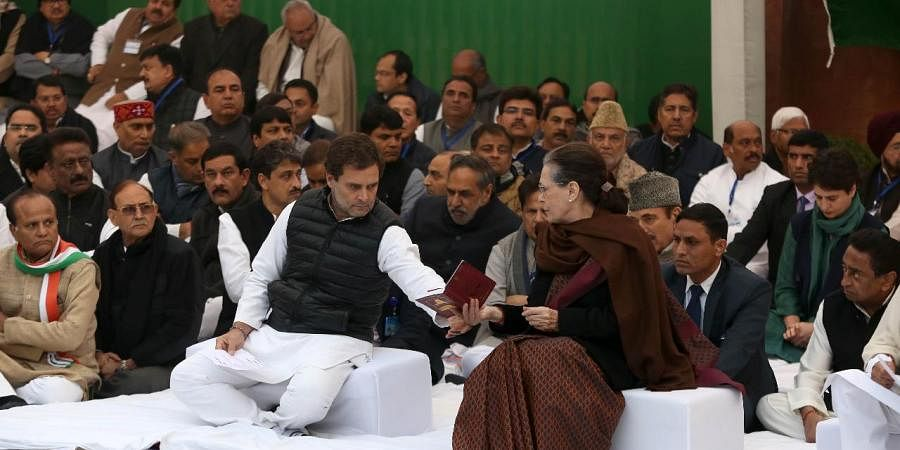 Congress chief Sonia Gandhi and Rahul Gandhi during dharna at Rajghat in New Delhi on Monday