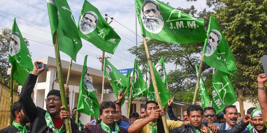 Jharkhand Mukti Morcha supporters celebrate the party's success in the Assembly polls on the counting day in front of the residence of the party chief Shibu Soren in Ranchi Monday