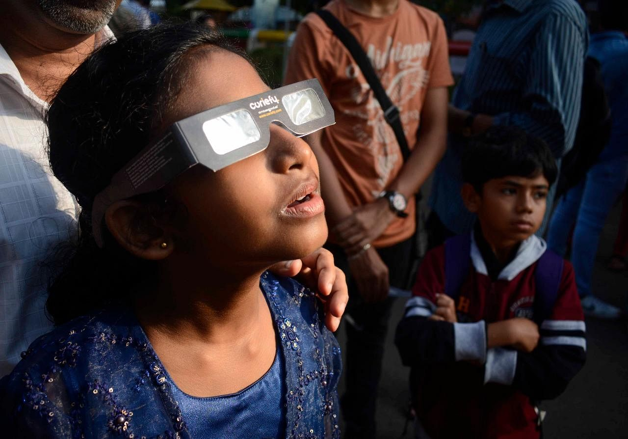A girl looking up at the crescent sun through a sun filter. According to experts, people should not look directly at the Sun during the eclipse without proper protection as it can damage the eyes. Instead, solar filters, pinhole camera or a telescopic projection can be used.