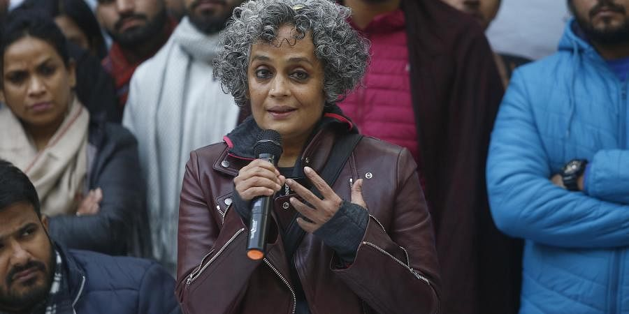 Writer-activist Arundhati Roy speaks as economist Arun Kumar, seated next to her, looks on during a protest against the amnended Citizenship Act at Delhi University campus in New Delhi