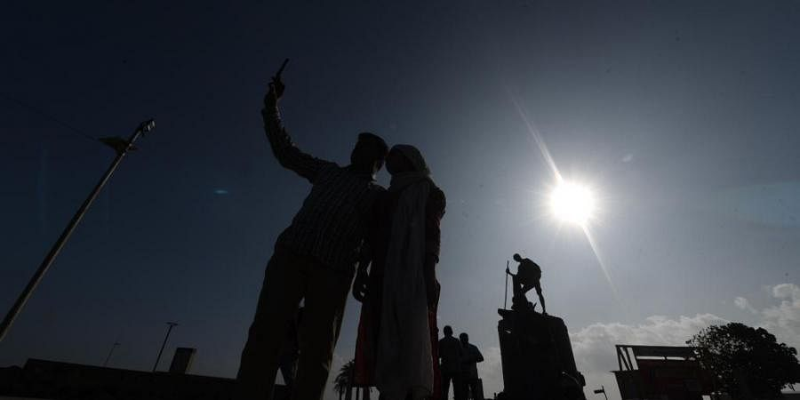 People seeing through the sun filter of Annular Solar Eclipse at marina beach, in Chennai on thursday. (Photo | Express / R.Satish babu)