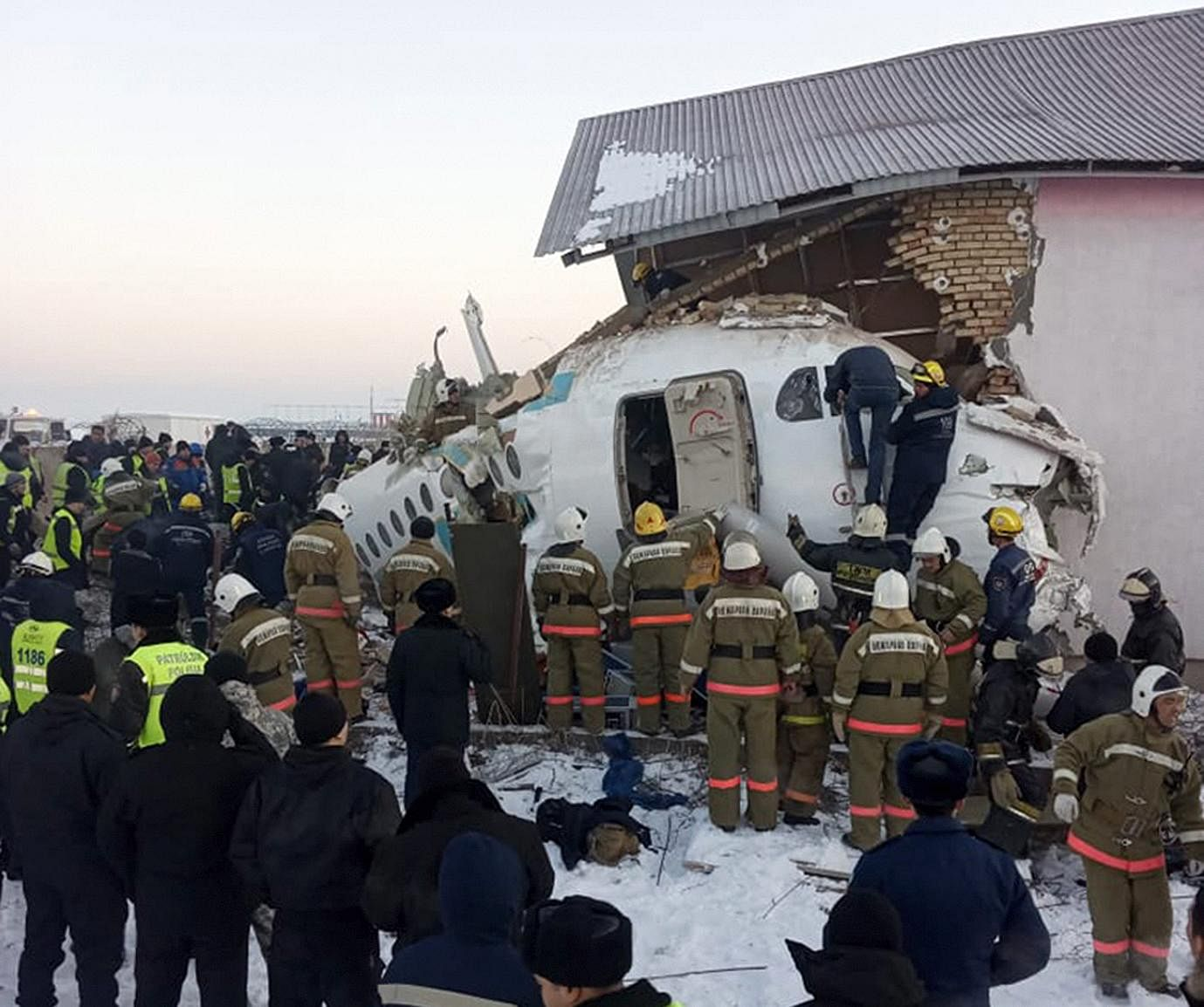 In this handout photo provided by the Emergency Situations Ministry of the Republic of Kazakhstan, police and rescuers are seen working on the site of a plane crash.