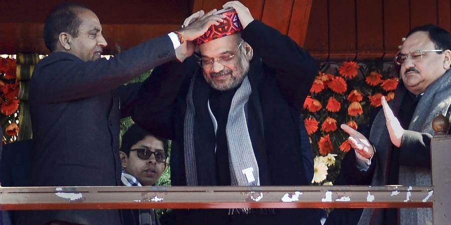 Union Home Minister Amit Shah being presented a traditional Himachali cap by CM Jai Ram Thakur as BJP working President JP Nadda looks on during a rally organised on the occasion of completion of two years by Himachal Pradesh's BJP government at Ridge in