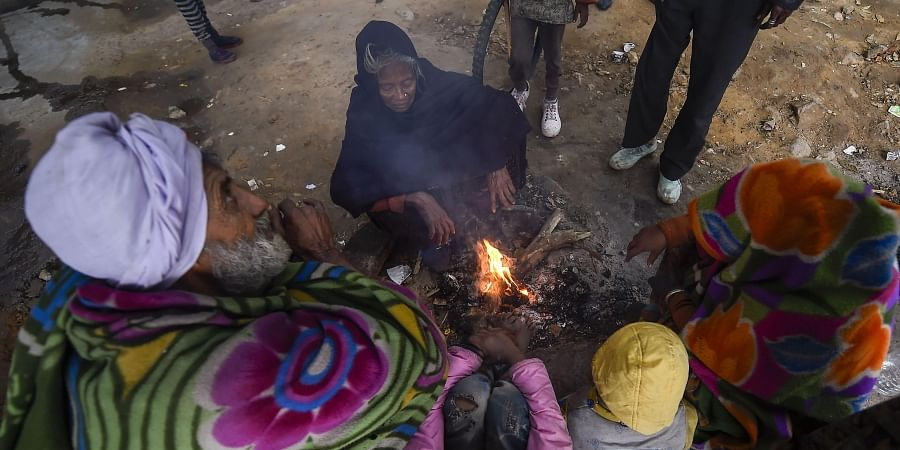 People warm themselves around a bonfire on a cold wintry morning in New Delhi Friday Dec. 27 2019. (Photo   PTI)
