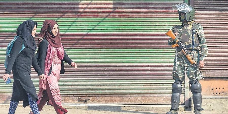 Kashmiri women walk past security guards in J&K