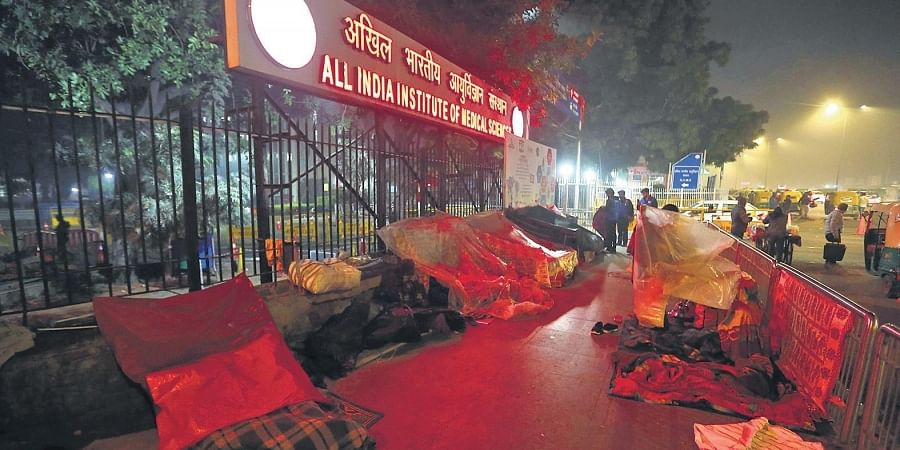People sleep in the cold on a pavement adjoining the AIIMS hospital in New Delhi on Friday night.