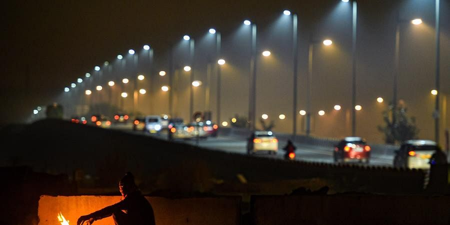 A man warms himself by a bonfire as cars ply in the background on a cold and wintry night in New Delhi. (Photo | PTI)