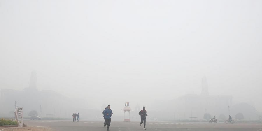 Joggers exercise at Raisina Hills on a cold foggy morning in New Delhi on on Saturday