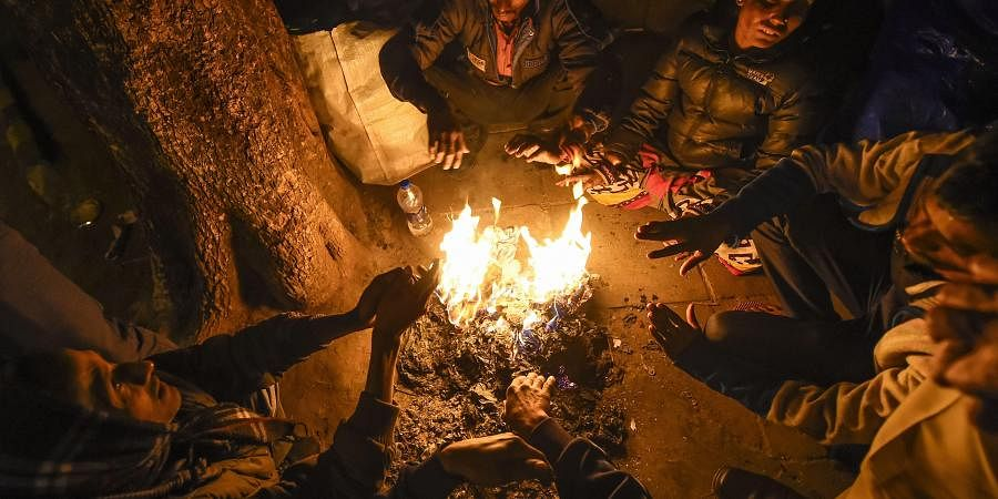 Workers warm themselves at a bonfire on a cold winter