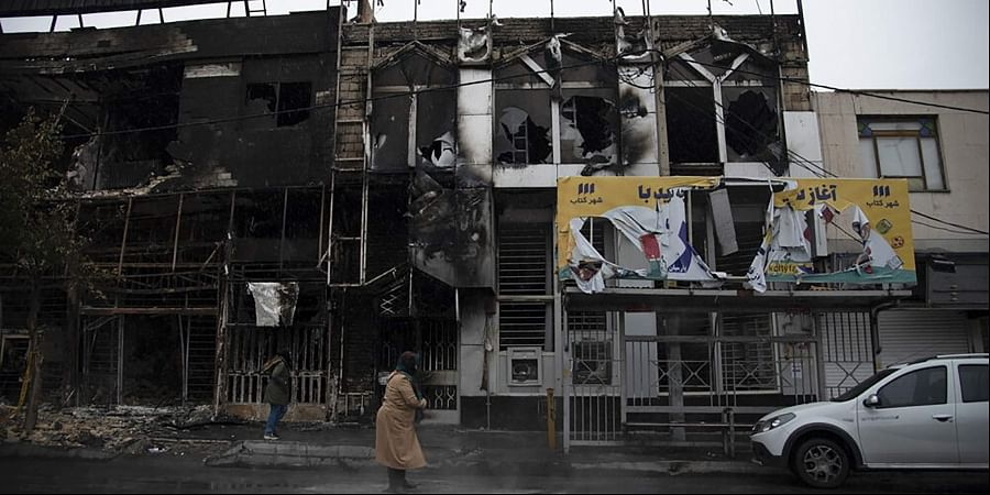 People walk past buildings which burned during protests that followed the authorities' decision to raise gasoline prices, in the city of Karaj, west of the capital Tehran, Iran. (Photo   AP)