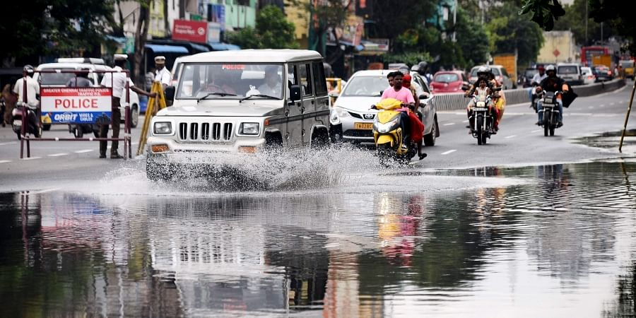 Commuters drive through waterlogged Kamarajar Promenade near All India Road in Chennai on Monday. (Photo | Debdatta Mullick/EPS)