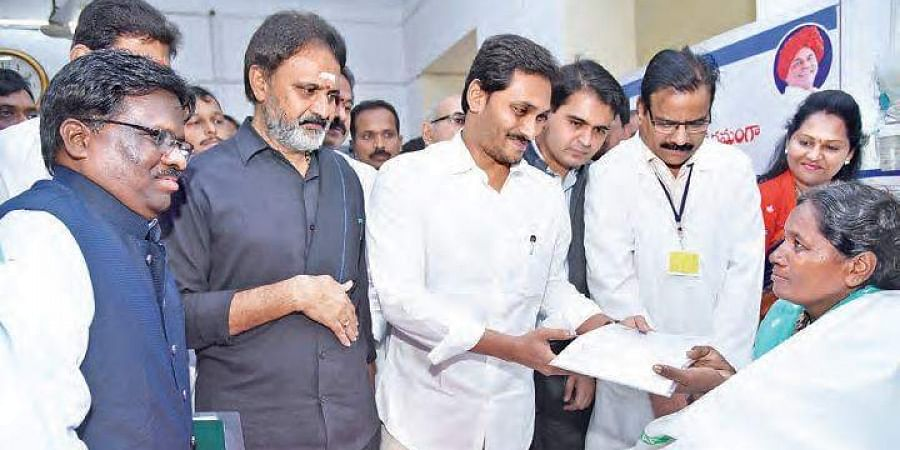 AP CM YS Jagan Mohan Reddy hands over cheques to the patients under Aarogyasri Aasaraa programme at Guntur Government Hospital on Monday.