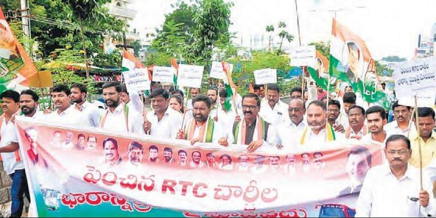 Workers of the Congress party take out a rally in Khammam town in protest against hike in bus fares.