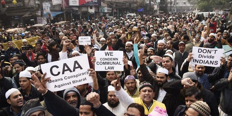Demonstrators hold placards and raise slogans during a protest against the Citizenship Amendment Act (CAA) and National Register of Citizens (NRC), at Jama Masjid in New Delhi on Friday.