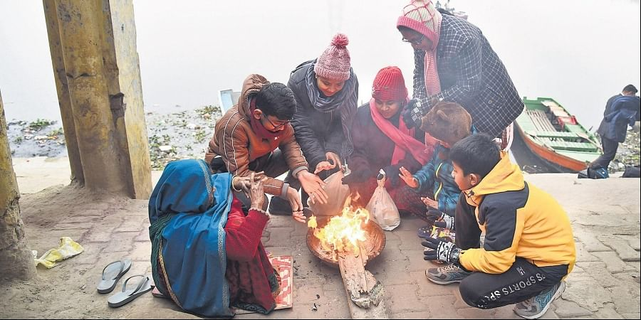 People huddle around a small fire to keep themselves warm on a cold winter morning, near Yamuna Ghat in New Delhi on Sunday.