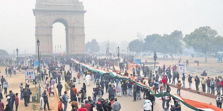 Demonstrators, protesting the alleged police action on CAA agitators, hold the tricolour in front of the India Gate, in New Delhi on Monday.