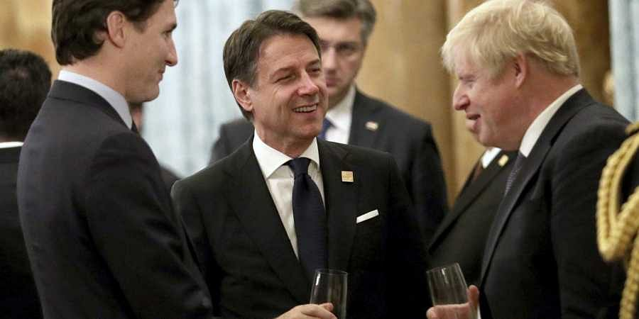 UK PM Boris Johnson talks to Canadian PM Justin Trudeau (L) and Italian Prime Minister Giuseppe Conte during a reception at Buckingham Palace
