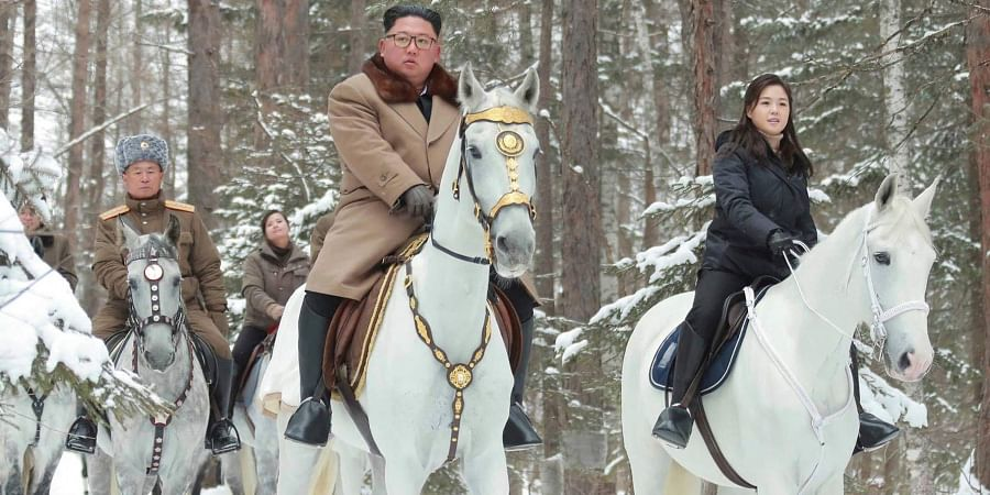 North Korean leader Kim Jong Un (C) with his wife Ri Sol Ju (R) rides on white horse during his visit to Mount Paektu, North Korea