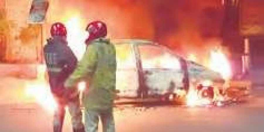 Fire personnel try to put off the flames that erupted from a car in Banjara Hills on Tuesday